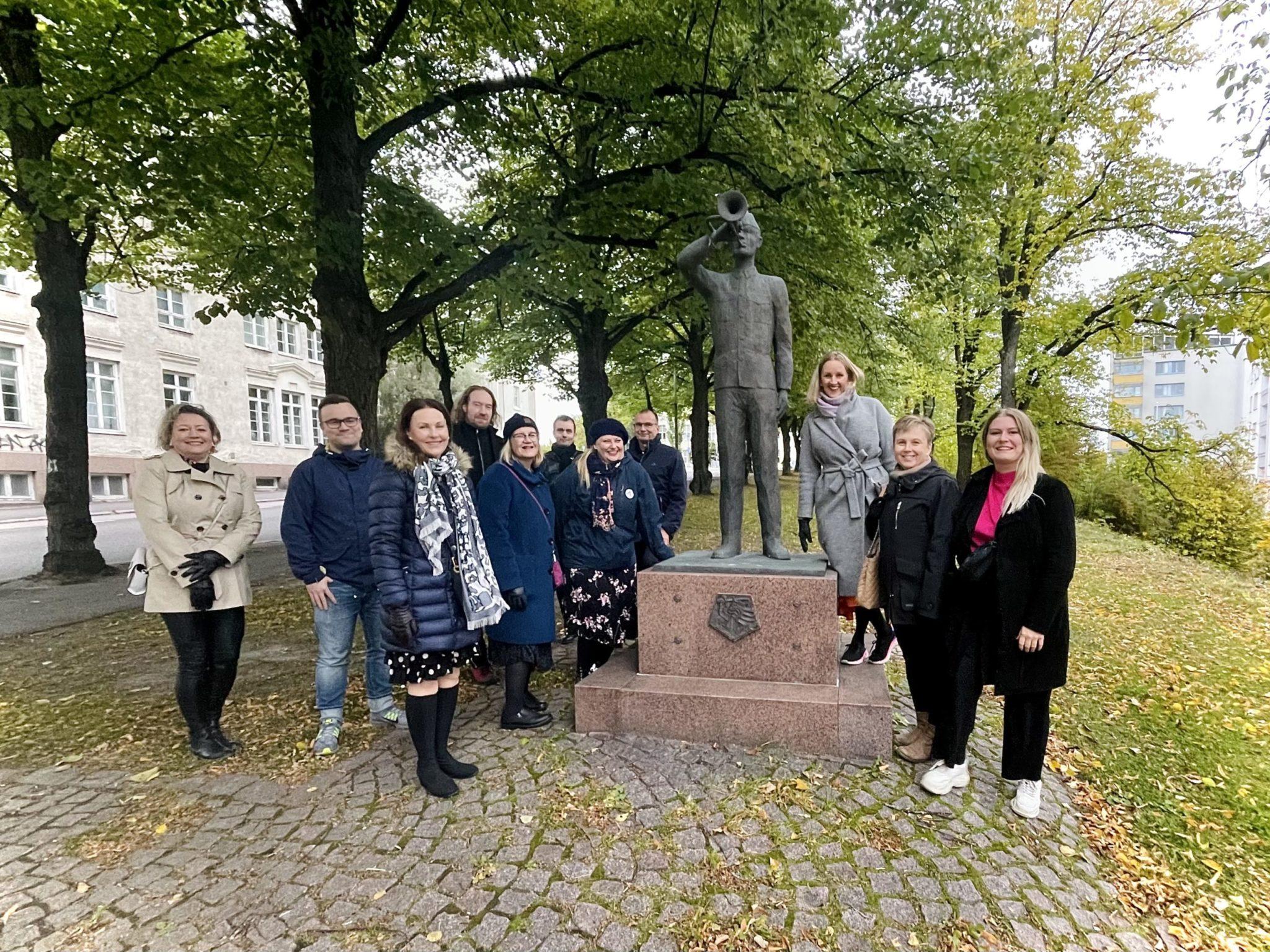 En staty och Luckannätverkets representanter i gruppbild