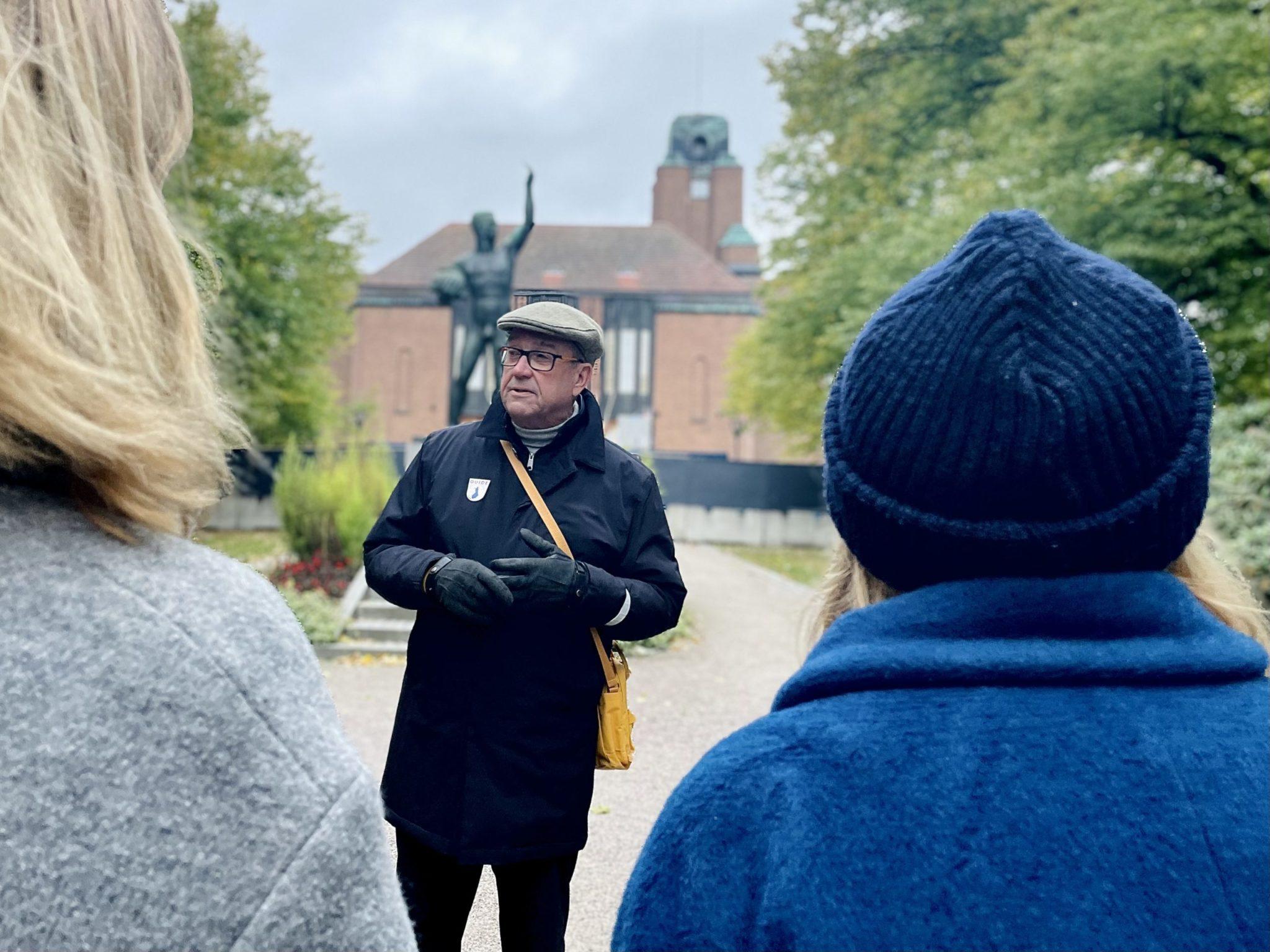 Guiden och två lyssnare står vid en staty